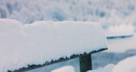 Wooden fence covered with fresh snow in winter.