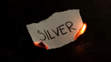Silver word written on white paper burns. Fire with smoke and ashes on black background Reklamní fotografie