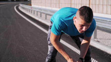 young fit man jogging outdoors, exhausted taking a rest on a empty street