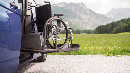Photo of black electric lift specialized vehicle for people with disabilities. Empty wheelchair on a ramp with nature and mountains in the back Reklamní fotografie