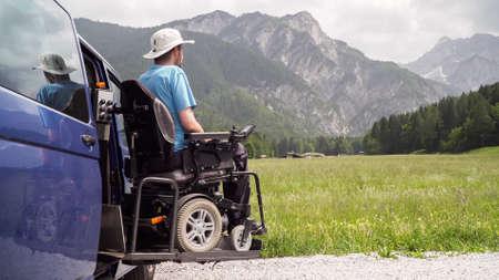 Vehículo especializado en elevador eléctrico para personas con discapacidad. Silla de ruedas vacía en una rampa con naturaleza y montañas en la parte de atrás