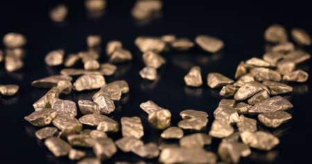 Shiny Gold Nuggets Falling on Black Background Stock Photo