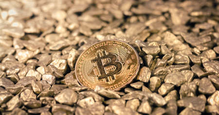 Golden Bitcoin Coin on a pile of Gold nuggets. Blockchain cryptocurrency, store of value. Digital gold concept.