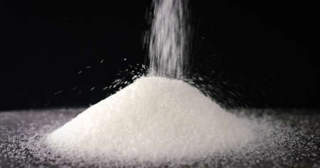 White Sugar or Salt falling in slow motion on a table on black background