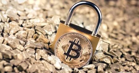Bitcoin blockchain security concept with key lock on gold pile background