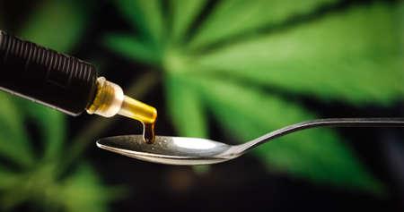 CBD Paste, Hand holding Syringe of Cannabis oil put on Spoon against Marijuana plant. Alternative Medicine Stock Photo