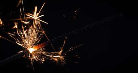 Firework festive sparkler burning on black background