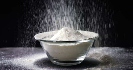 Flour is falling into a bowl in slow motion on black background Stock Photo