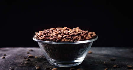 Roasted Coffee beans closeup in a glass bowl on a black background