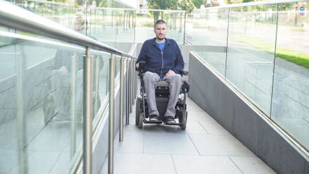 man on electric wheelchair using a ramp. Accessibility concept Reklamní fotografie