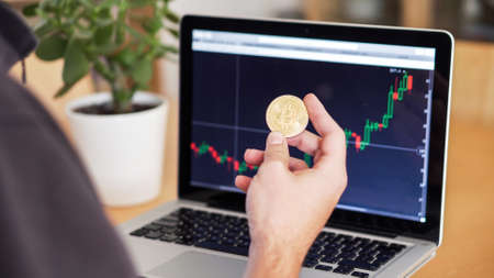man checking cryptocurrency chart and bitcoin coins on a laptop