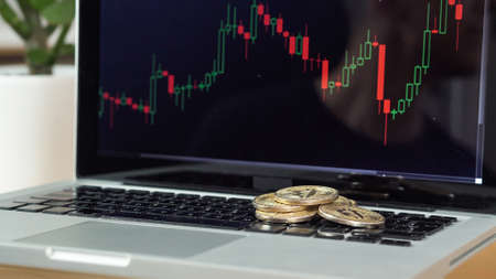 Bitcoin coins on a laptop with price chart in the background