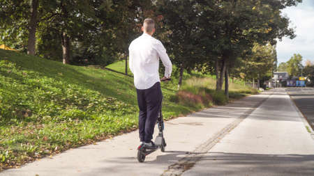 Young casual business student man riding electric scooter on a sidewalk in summer Stock Photo