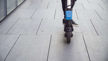 Closeup of young casual business student man riding electric scooter on a sidewalk in a business city