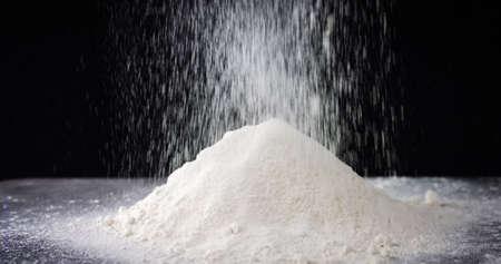Pile of white flour falling on black background