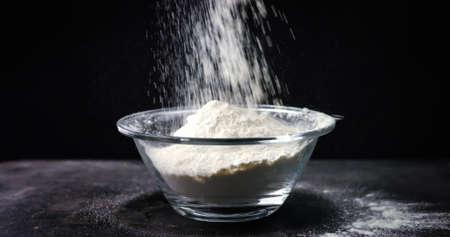Flour is falling into a bowl in slow motion on black background Reklamní fotografie