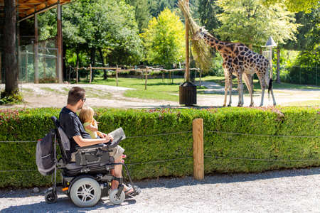 Disabled Father in Wheelchair enjoying Nature with Daughter Girl in Outside zoo park on a sunny day.