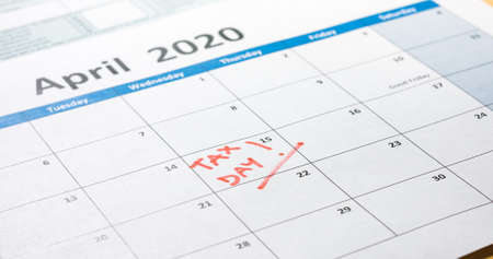 Writing tax day on 2020 April 15 calendar with red marker. Deadline for 1040 form return.