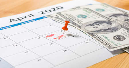 Red pin marked at April 15 for tax day with dollars falling on 2020 calendar.