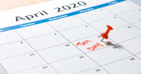 Writing and pinning tax day on calendar for april 15 with red color. Reklamní fotografie