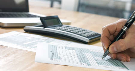 Closeup of US tax form 1040 and businessman hand calculating and filling report paper at the office. Foto de archivo