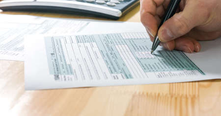 Closeup of US tax form 1040 and businessman hand calculating and filling report paper at the office.