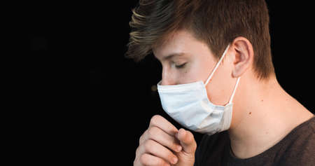 Teenager wearing face mask coughing. Coronavirus and Flu epidemic concept. Reklamní fotografie
