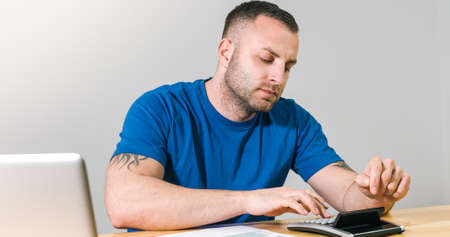 Man filling 1040 US tax form by hand with calculator and laptop. Reklamní fotografie