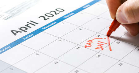 Writing tax day deadline reminder on April 15 2020 with 1040 form and calculator. Reklamní fotografie