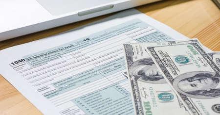 U.S. 1040 tax return form with 100 usd dollar bills.
