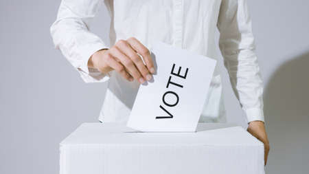 Person casting vote into the ballot box at elections. Human hand voting. 版權商用圖片