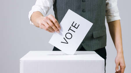 Businessman casting vote into the ballot box at elections. Human hand voting.