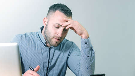 Frustrated businessman under stress nervously filling 1040 tax form with calculator at office desk.