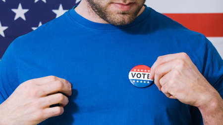 Man putting on Vote button for Presidential election 2020 in America.