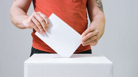 Young casual and tattooed man casting vote into the ballot box at elections. Human hand voting.