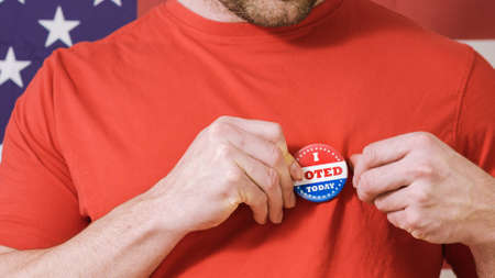 Man putting on I Voted Today button for Presidential election 2020 in America. Banque d'images