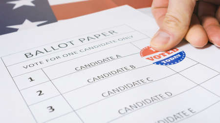 Man hand marks selected candidate with I Voted Today sticker on a paper ballot for US Presidential Elections.