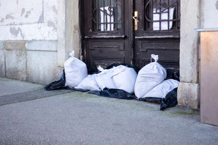 Sandbags stacked in front of doors to protect against flooding of river or sea. 版權商用圖片