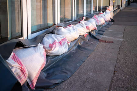 Sandbags stacked in front of doors to protect against flooding of river or sea. Stock Photo