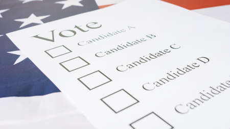Voting for Presidential elections 2020 with ballot on American flag.
