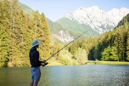 Man fishing at lake in a beautiful green nature