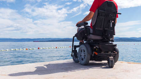Man sitting in a wheelchair on the beach. Dangers of jumping into water from heights. Head and spine injury.