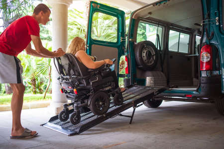 Driver assisting disabled person on wheelchair with transport using accessible van with ramp.