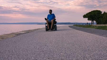 Man on wheelchair near sea at sunset.