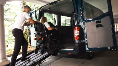 Woman on wheelchair going into vehicle using an accessible ramp with assistant helping. Stockfoto