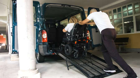 Wheelchair user leaving vehicle adapted for disabled transport with ramp and lift. Stock Photo