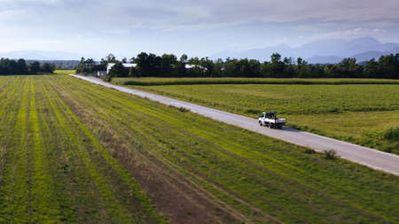 Aerial shot of a small truck driving on a rural road with farming fields.