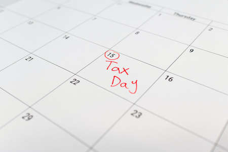 Tax day marked on April 15 calendar with red marker. Deadline for 1040 form return. Stockfoto