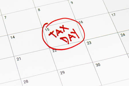 Tax day marked on April 15 calendar with red marker. Deadline for 1040 form return.