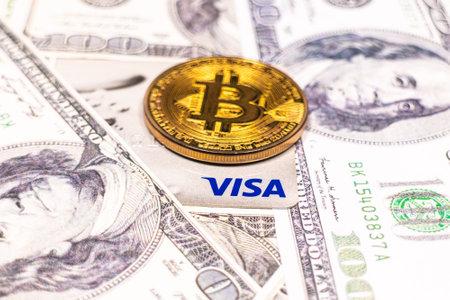 SLOVENIA, LJUBLJANA - March 2, 2021: Bitcoin coin and Visa credit card on dollar bills. Redakční